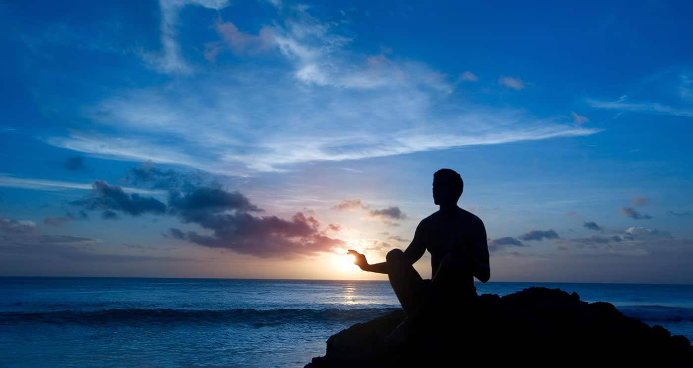Meditating man captures the distant sun at a beach